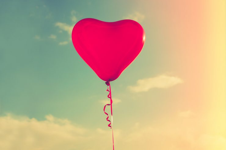 beautiful red hart shape balloon against sky with clouds, retro colors, sun flare